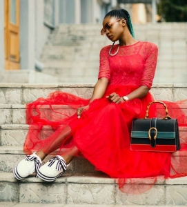 woman wearing red long sleeved dress near black leather bag sitting on concrete stairs posing for photoshoot